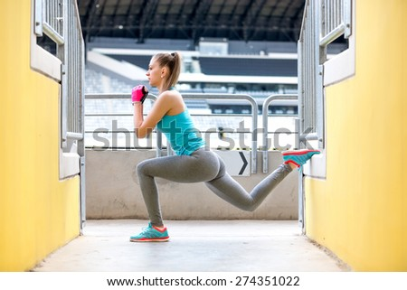 Female runner stretching and doing squats after jogging training. Fitness concept on stadium - stock photo