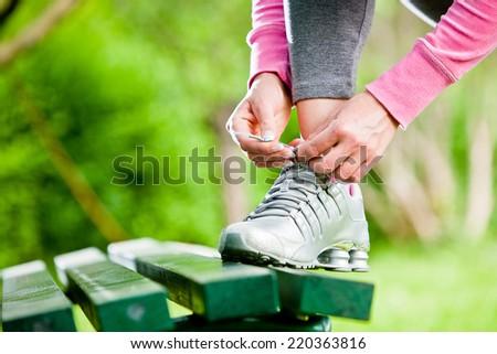 Female runner tying her shoelace outdoor - stock photo