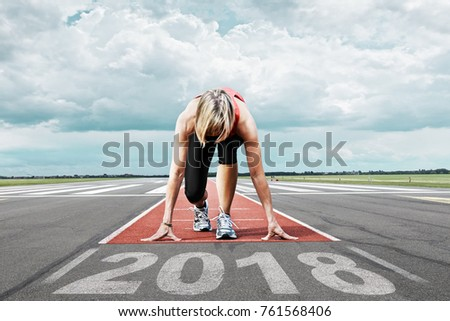 Female runner waits for her start at an airport runway. In the foreground the painted date 2018 symbolises the start into the new year.