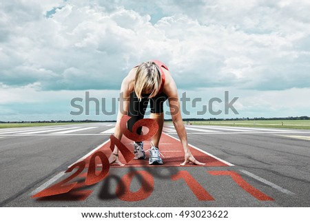 Female runner waits for the start on an airport runway. In the foreground the view of the peeling date 2016 and the date 2017 on the ground.