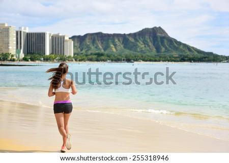 Female runner woman running jogging on beach run. Girl athlete fitness runner jogger training living healthy active exercise lifestyle exercising outdoor on Waikiki Beach, Honolulu, Oahu, Hawaii USA - stock photo