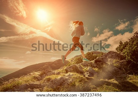 Female running in mountains under sunlight. - stock photo