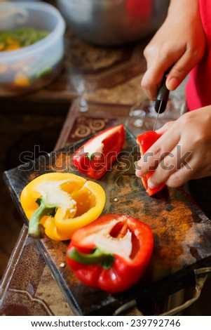 female's hand cutting big chili pepper for making food - stock photo