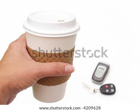 female's hand holding disposable coffee cup with keys and cell phone in background - stock photo