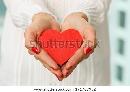 Female's hands presenting a red heart
