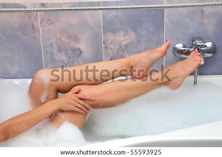 female's legs with a hand in the bathroom