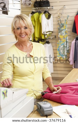 Female sales assistant in clothing store - stock photo