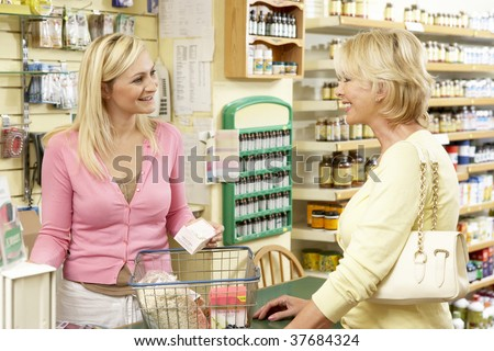 Female sales assistant in health food store - stock photo