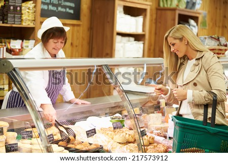 Female Sales Assistant Serving Customer In Delicatessen - stock photo