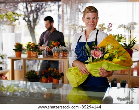 Female sales assistant working as florist and holding bouquet with customer in background. Horizontal shape, waist up - stock photo