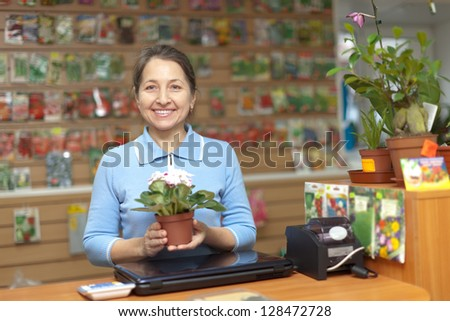 Female saleswoman with flower in pot at store for gardener