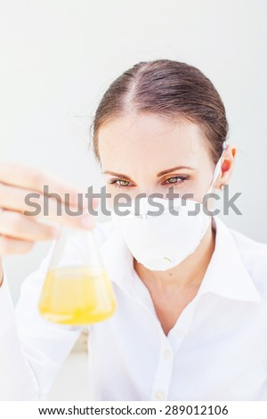 female scientist holding a flask of yellow solution - stock photo
