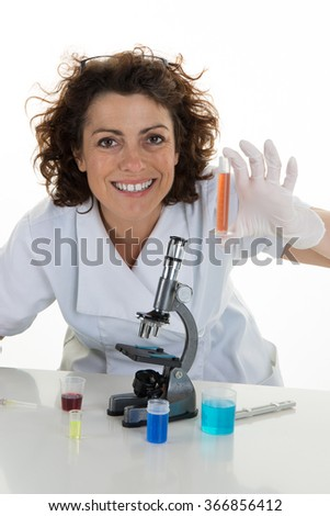 Female scientist holds test tube using tongs, also dropping some red fluid to the tube, wears gloves and goggles, studio shoot isolated on white background - stock photo