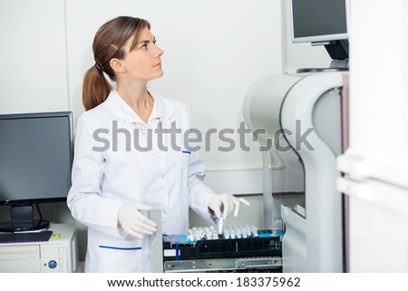Female scientist loading coagulation analyzer with test samples in lab