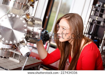 Female scientist looking to the laser deposition chamber - stock photo