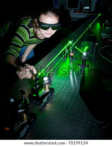 female scientist working with lasers while doing research in a quantum optics lab - stock photo