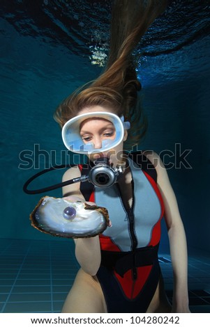Female scuba diver and pearl - stock photo