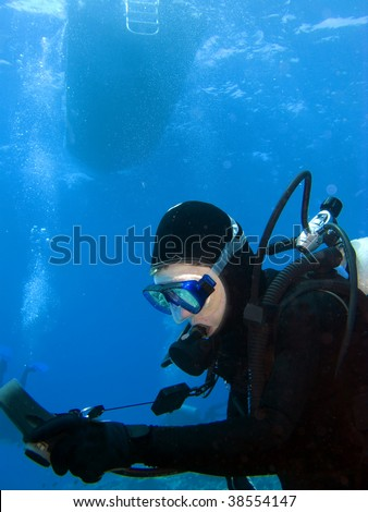 Female Scuba Diver checking Gauges under the Boat - stock photo