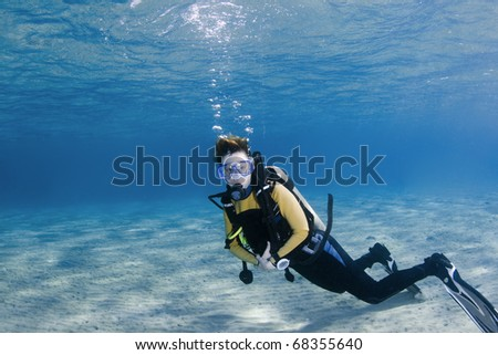Female scuba diver over white sand in clear blue water - stock photo