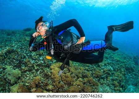 Female SCUBA diver posing underwater - stock photo