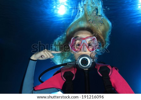 Female scuba diver show the underwater sign for ear problems  - stock photo