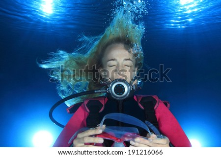 Female scuba diver underwater without mask  - stock photo