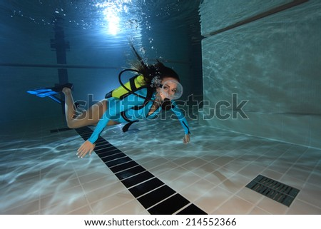 Female scuba diver with lycra suit swimming underwater in the pool  - stock photo