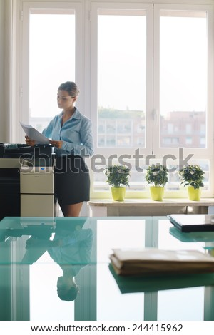 Female secretary working in office, copying document and paperwork with copy machine in modern office - stock photo