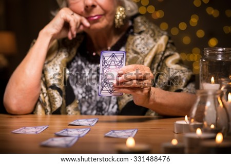 Female seer telling fortune from tarot cards - stock photo