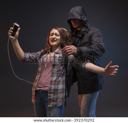 FEMALE SELF DEFENSE SERIES- Scary stranger grabs a teenage girl by her hair.  Teenage Girl on a cell phone gets attacked by a stranger. - stock photo