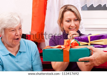 female senior and pretty daughter with gifts