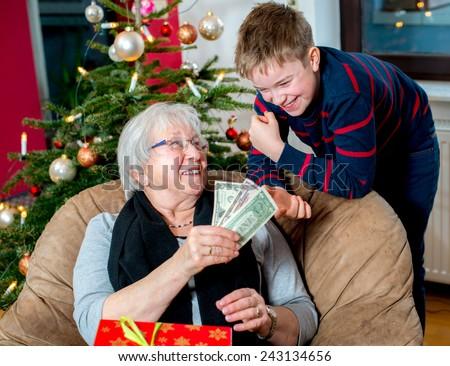 female senior has a money- gift for her grandson - stock photo