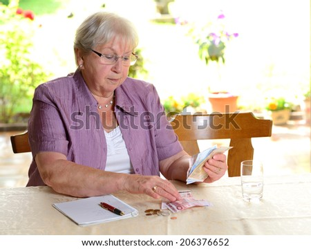 female senior is calculating her budget - stock photo