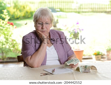 female senior is calculating her little budget - stock photo