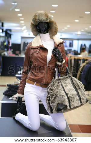 female shop mannequin dummy dressed in jacket with bag and hat - stock photo