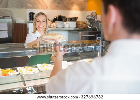 Female shop owner smiling while giving sandwich to customer in bakery - stock photo