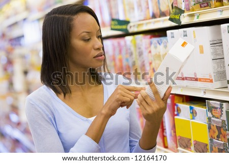 Female shopper checking food labelling in supermarket - stock photo