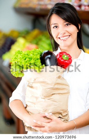 Female shopper holding a paper bag with groceries - stock photo