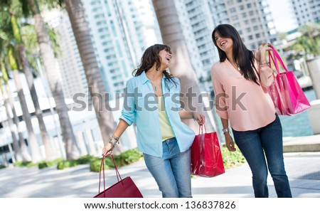 Female shoppers having fun and laughing while carrying baga - stock photo