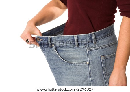 Female showing how much weight she has lost by wearing her old jeans that are sizes too big - stock photo
