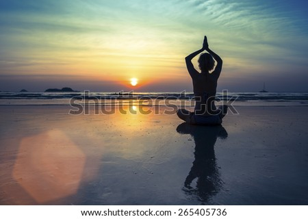 Female silhouette in Yoga meditation pose at amazing sunset. - stock photo