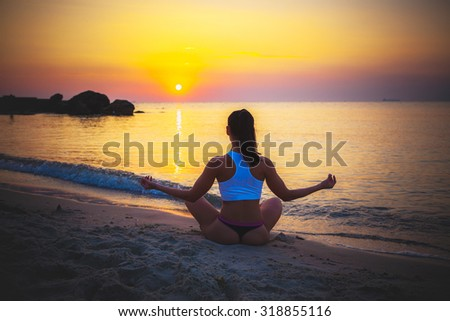 Female silhouette in Yoga meditation pose at amazing sunset