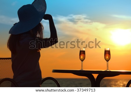 Female silhouette on sunset behind  table with two glasses - stock photo