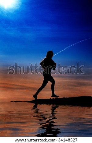 Female silhouette running at water
