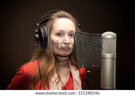 Female singer with headphones recording in studio - stock photo