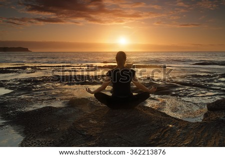 Female sitting by the ocean at sunrise meditating, wellness, health, spirituality. - stock photo