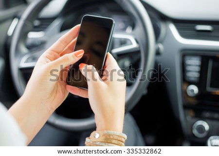 Female sitting in the car and texting - stock photo