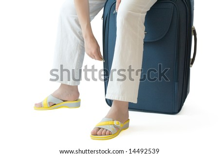 Female sitting on a  suitcase and zipping or unzipping it - stock photo