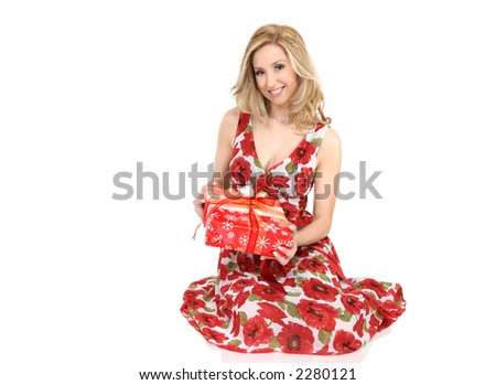 Female sitting on floor holds a festive wrapped present.