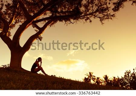 Female sitting under a tree. - stock photo